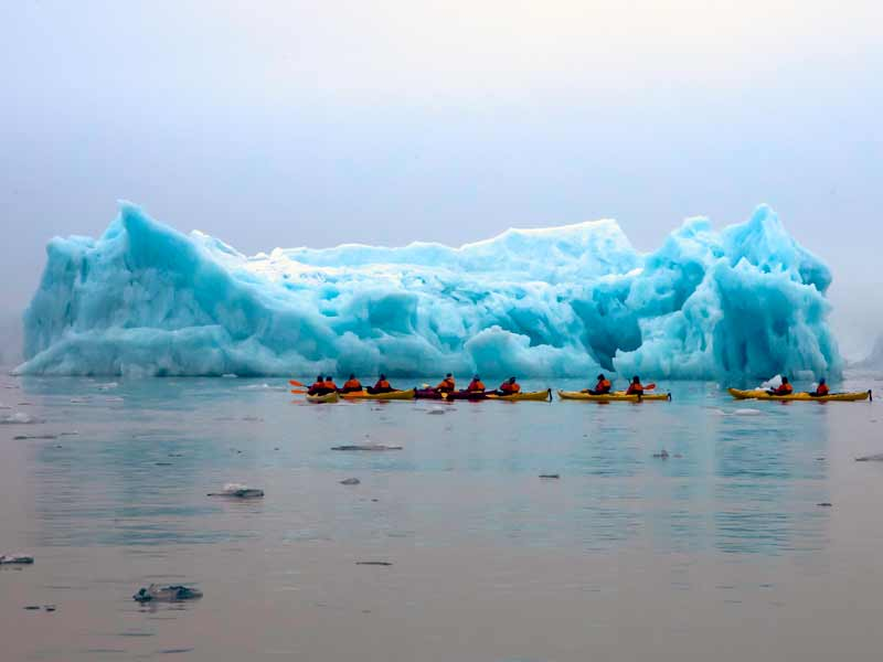 Kayakers near iceberg